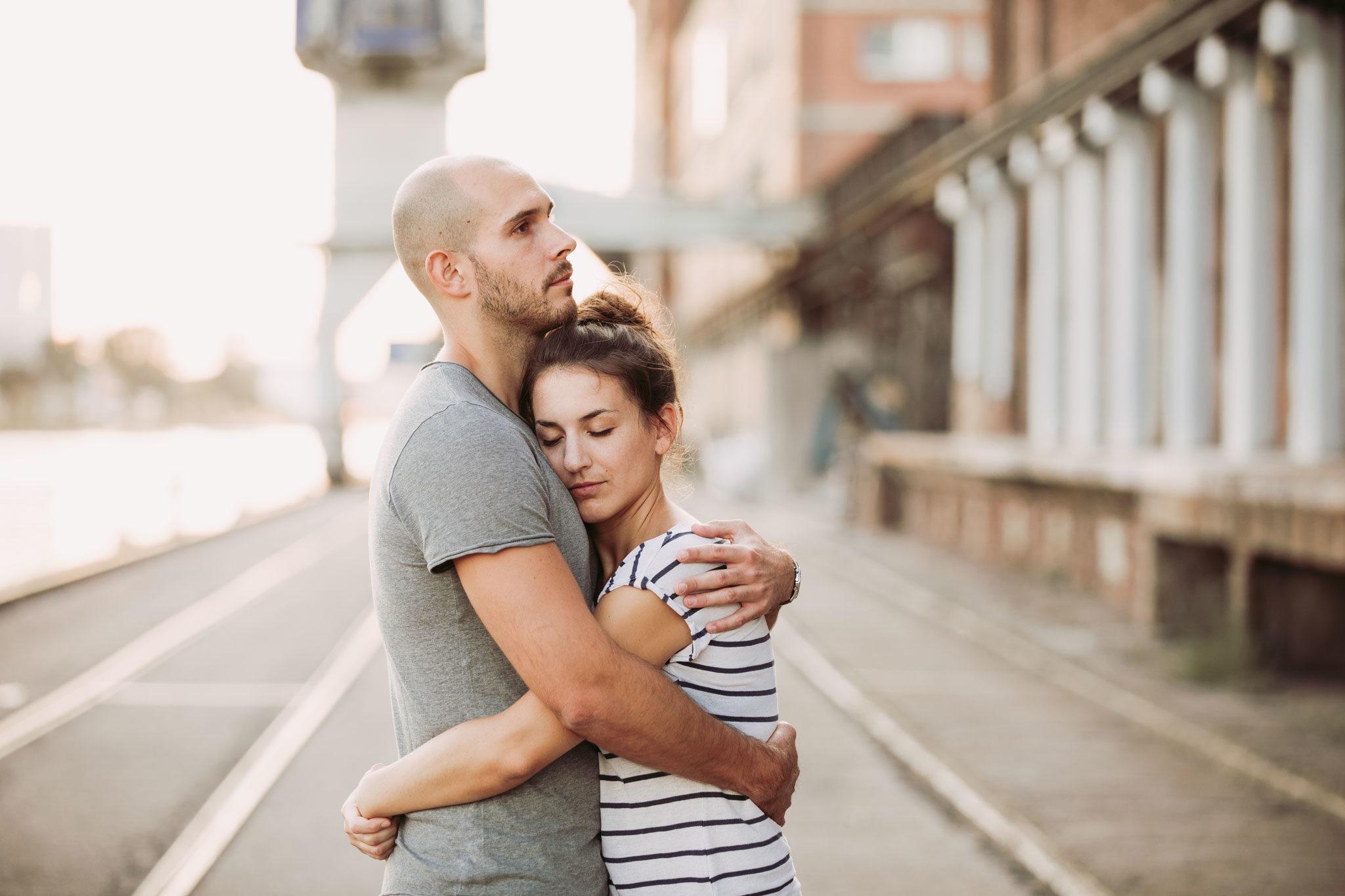 junges Paar steht engumschlungen in einer Industrielandschaft, Kai oder Hafen. Die junge Frau hat Ihren Kopf an die Brust des Mannes gelegt und die Augen geschlossen. Portfolio, Portraits