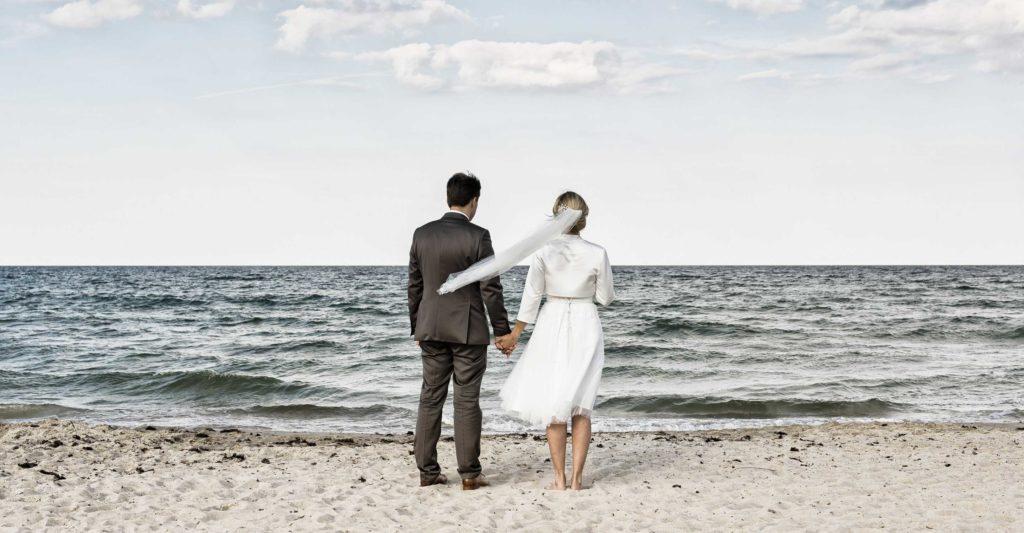 Portfolio, Brautpaar blickt auf das Meer, Ostsee, Wind, Wellen, Strand, Ernst Merkhofer, Hochzeiten, Wedding, Fotograf, Fotografie, home,