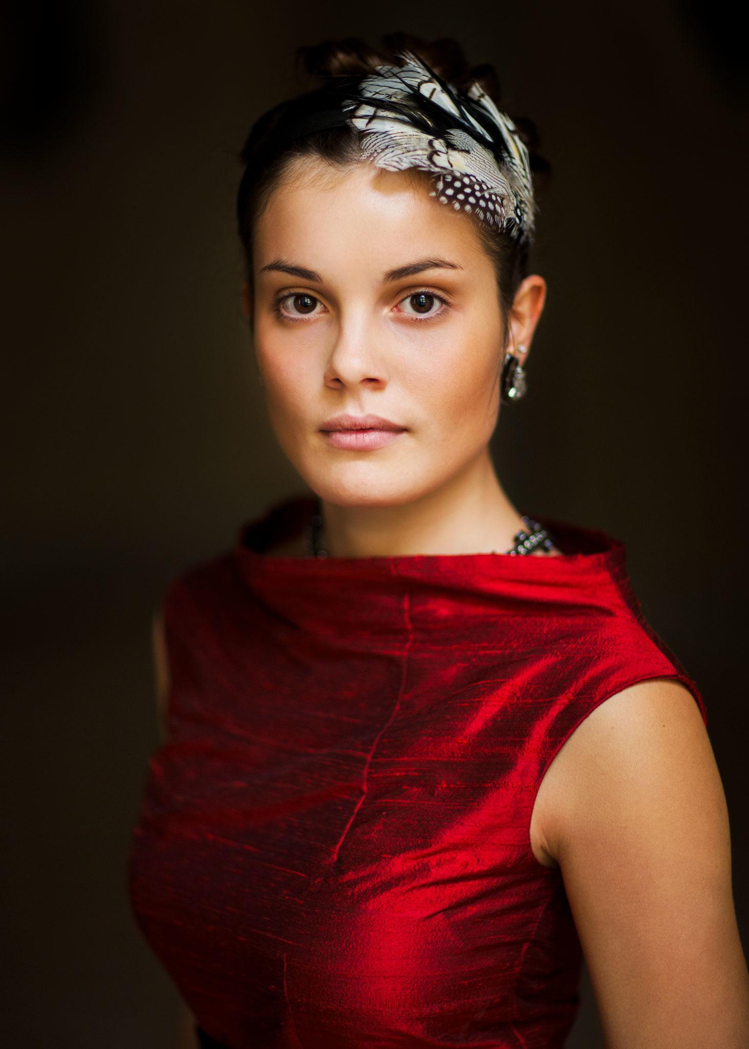 junge Frau in rotem Kleid und Haarschmuck schaut offen direkt in die Kamera, natürliches Fensterlicht mutet an wie gemalt. EMF Ernst Merkhofer Portraits, Portfolio,