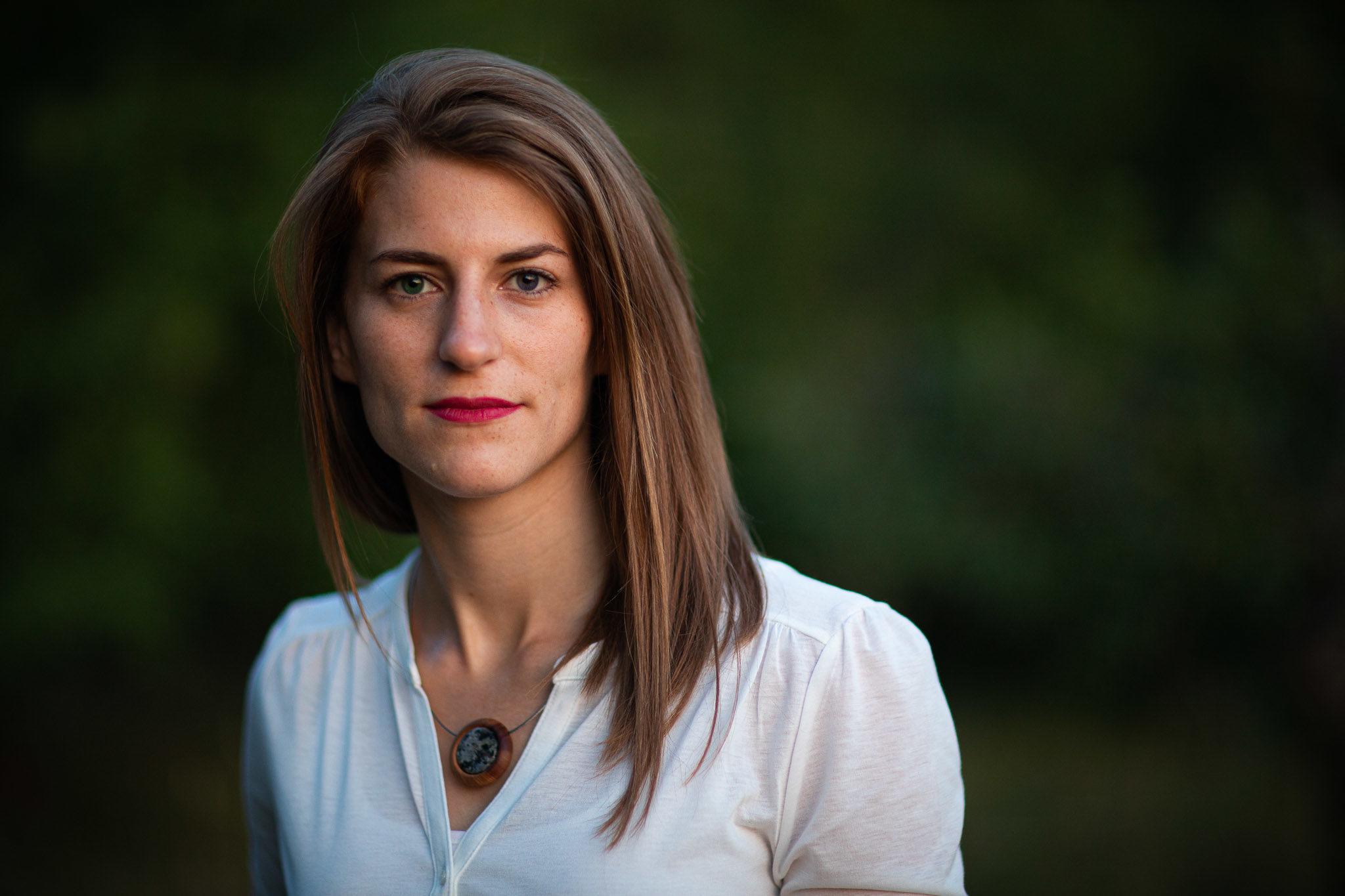 Outdoor portraits einer jungen Frau, blick direkt in die Kamera, Hintergrund dunkels, verschwommenens Blattgrün, offenes sehr weiches Abendlicht nach Sonnenunterang, Outdoor Portraits, Best Light.