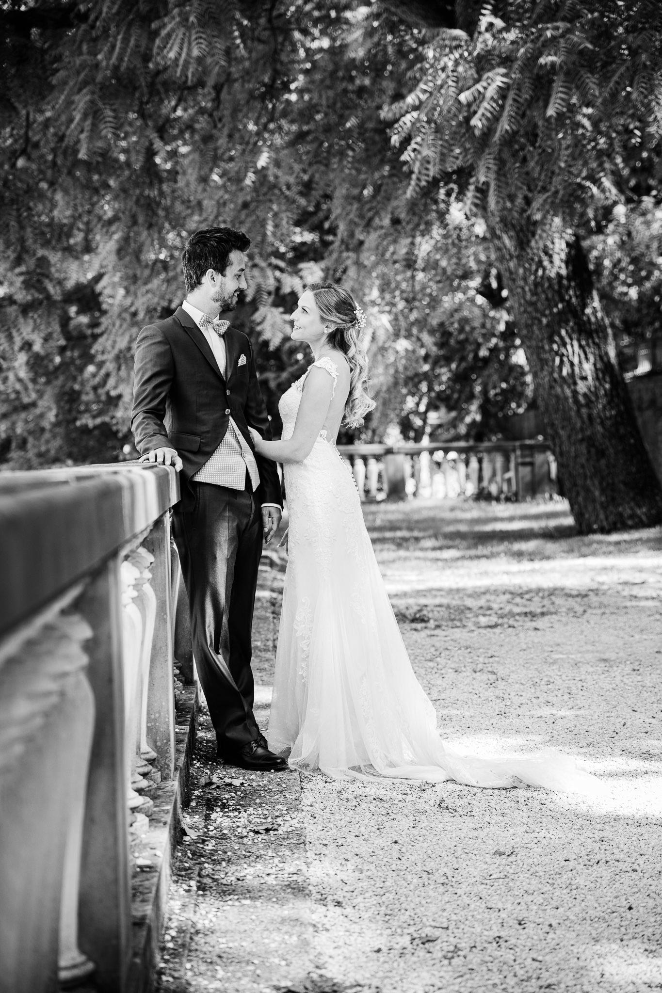 junges Brautpaar steht an einem Steingeländer im Heidelberger Schloßpark und schauen sich an. Fotosession nach der Hochzeit.