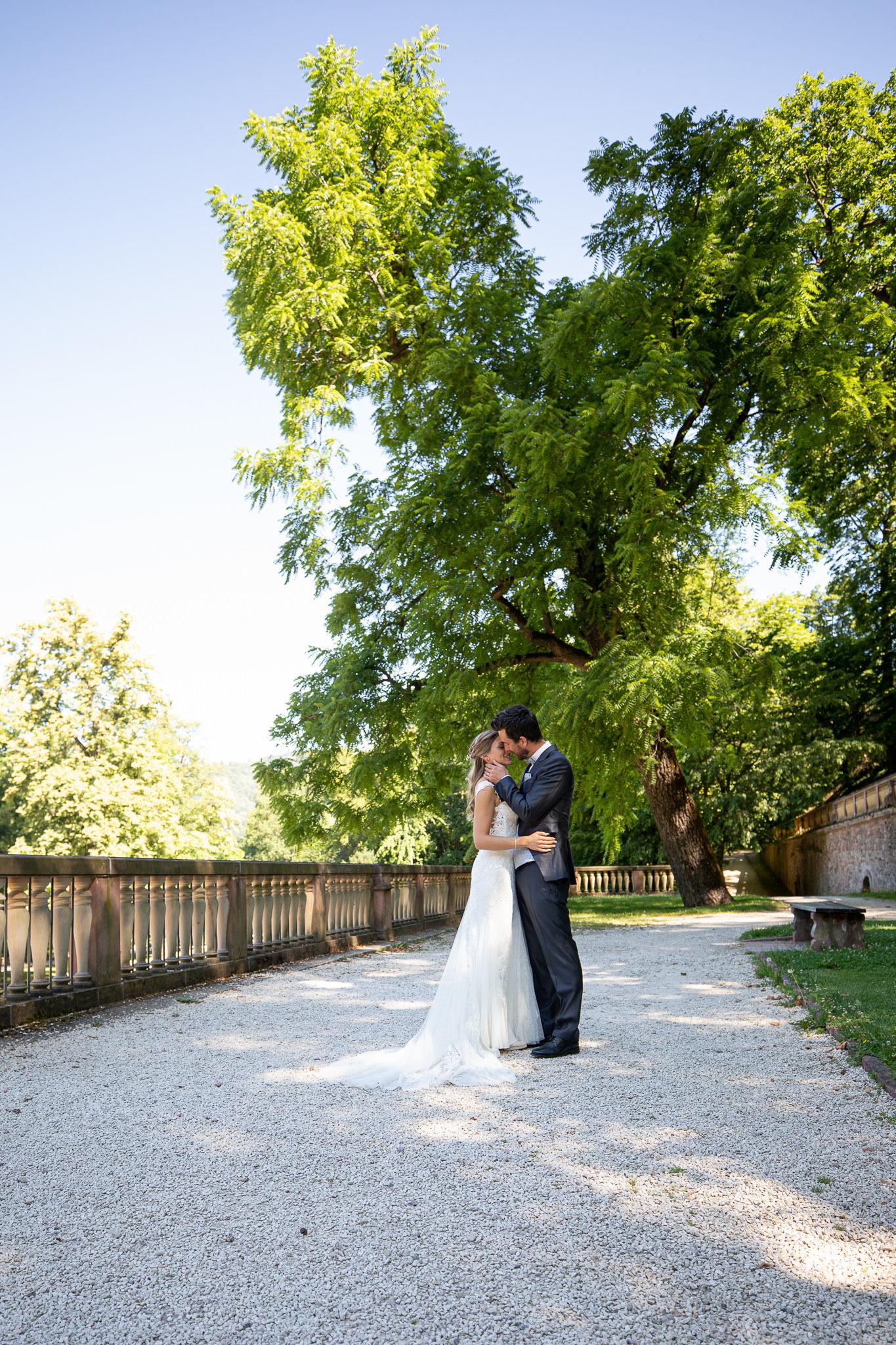 junges Brautpaar steht im Park mit großen Bäumen zärtlich umarmend bereit zum Kuss. After Wedding Shoot in Heidelberg Schloßpark