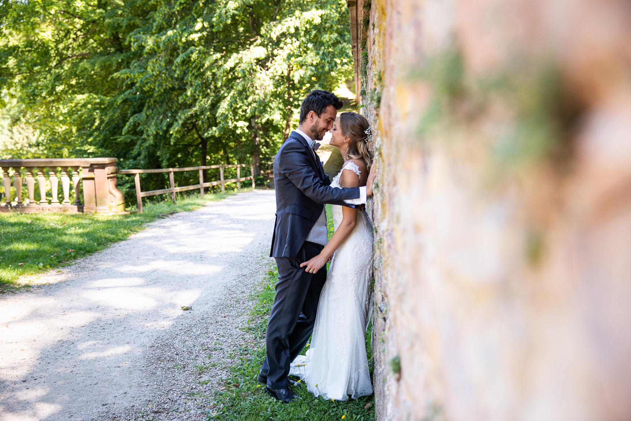 Braut steht mit dem Rücken an einer Steinmauer, der Bräutigam steht direkt vor Ihr und beugt sich Ihr entgegen, inniger Blickkontakt. Bilder nach der Hochzeit, After Wedding Shoot.