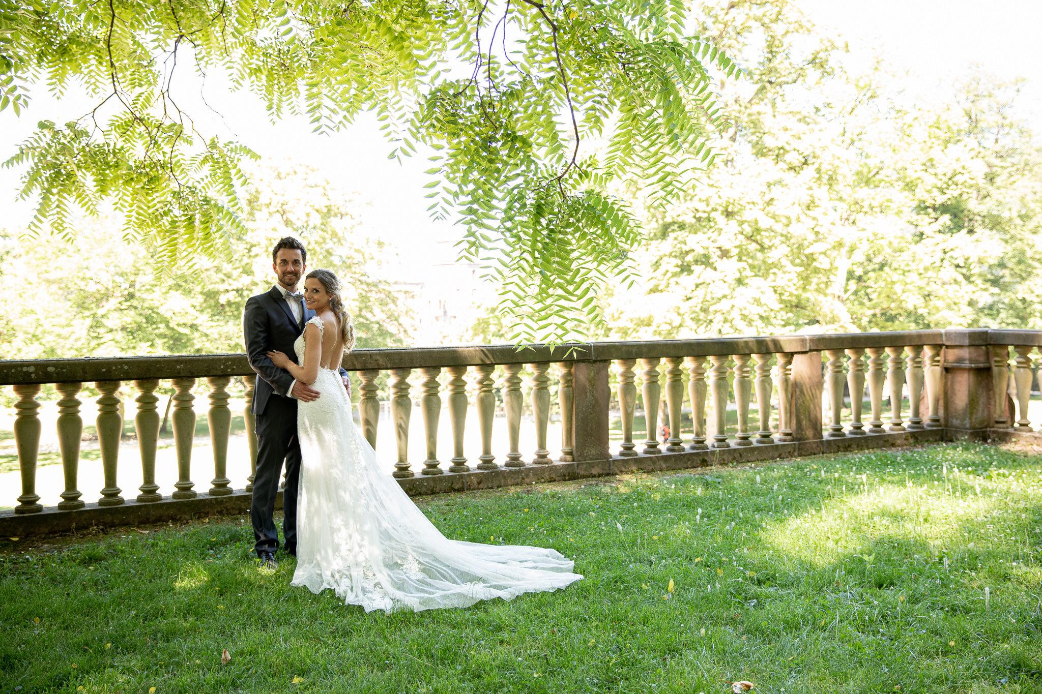 Brautpaar steht eng zusammen und blickt in die Kamera. Schlossgarten Heidelberg. After Wedding.