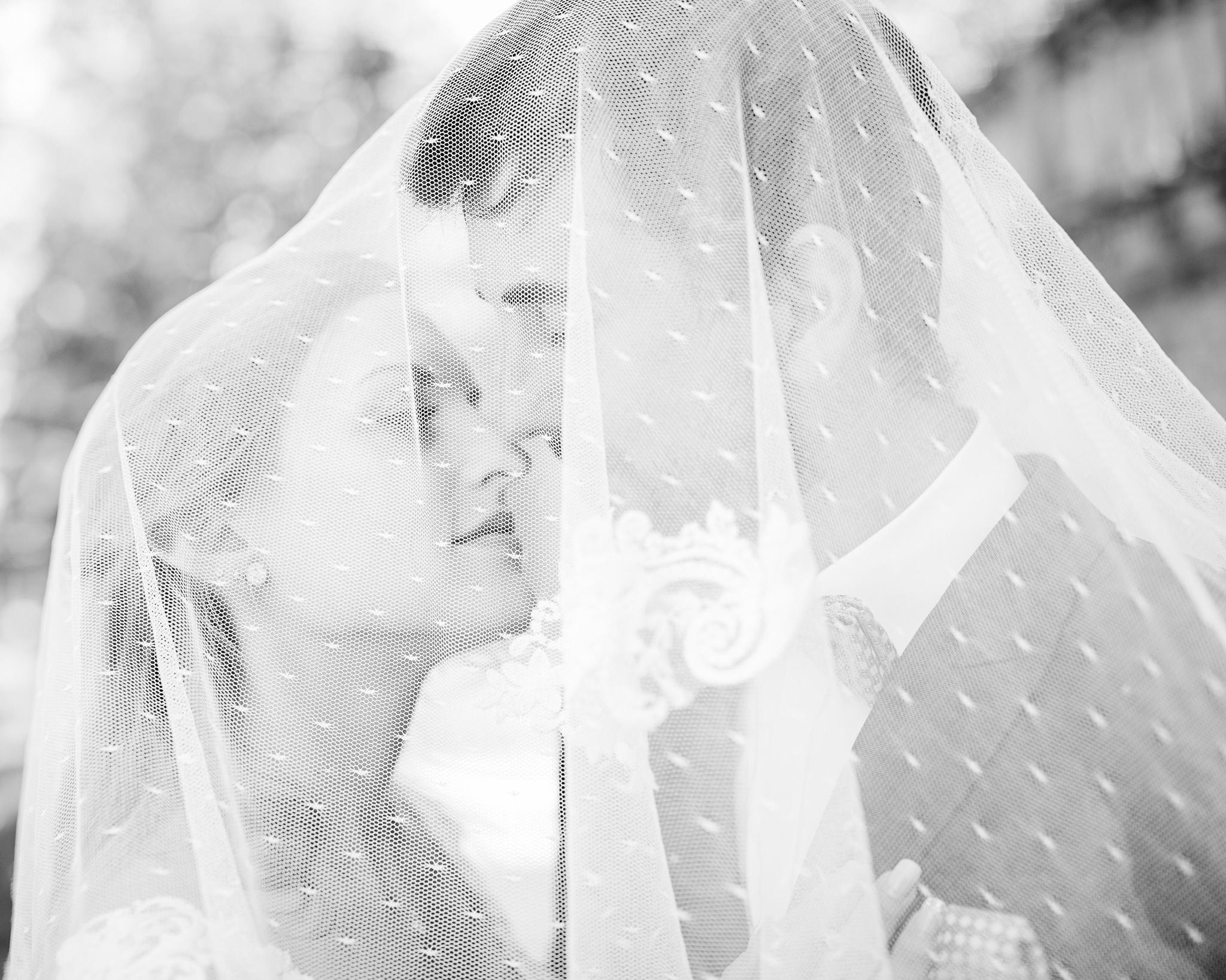 Das Brautpaar steht dicht beieinander und wird vom Schleier eingehüllt, Zärtlichkeit und Nähe, Schwarz-Weiß, After Wedding Shoot. Hochzeitsfotos und mehr, Ernst Merkhofer