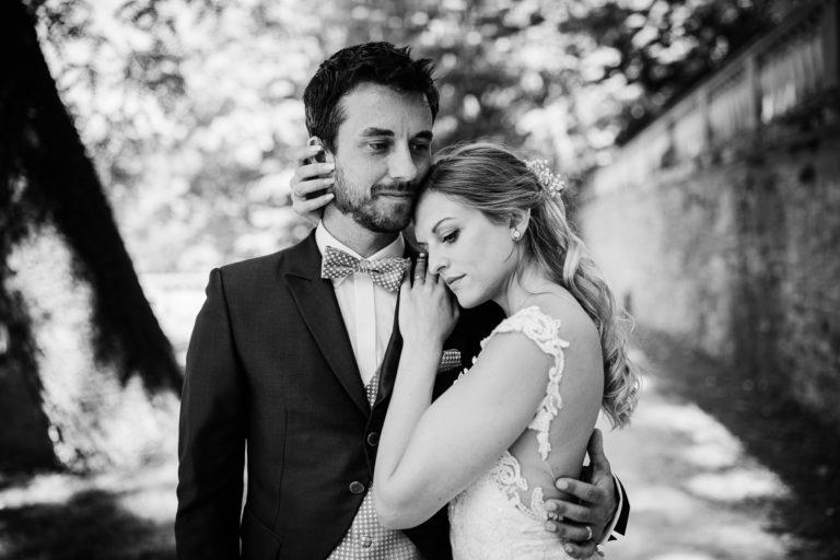 Braut hält Bräutigam und Bräutigam hält Braut in einer verträumten, inningen Umarmung. Die Stimmung zeugt von absolutem Vertrauen in den Partner. After Wedding Shoot im Schloßgaarten Heidelberg.