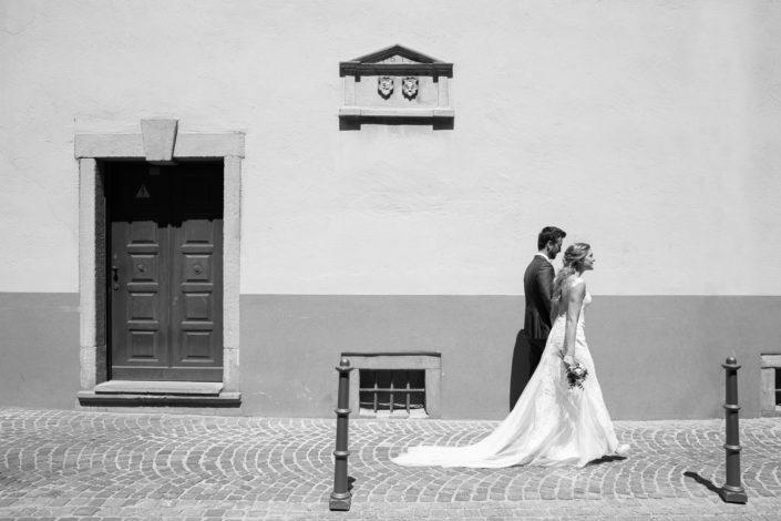 junges Brautpaar läuft die Straße entlang auf dem Weg zum After Wedding Shoot. Schwarz-Weiß Foto, hartes Mittagslicht Sonne,