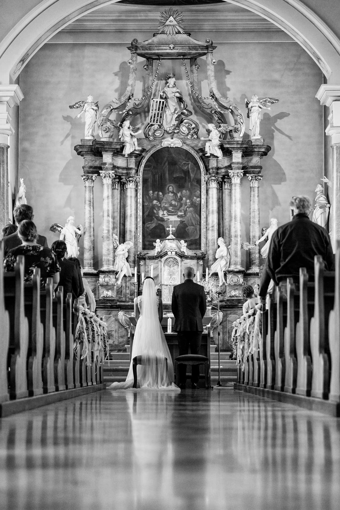 kirchliche Hochzeit, man sieht das Brautpaar von hinten. es steht am Altar. Tiefer Standpunkt der Kamera, verleiht dem Bild eine enorem Tiefe. Schwarz-Weiß . Hochzeiten