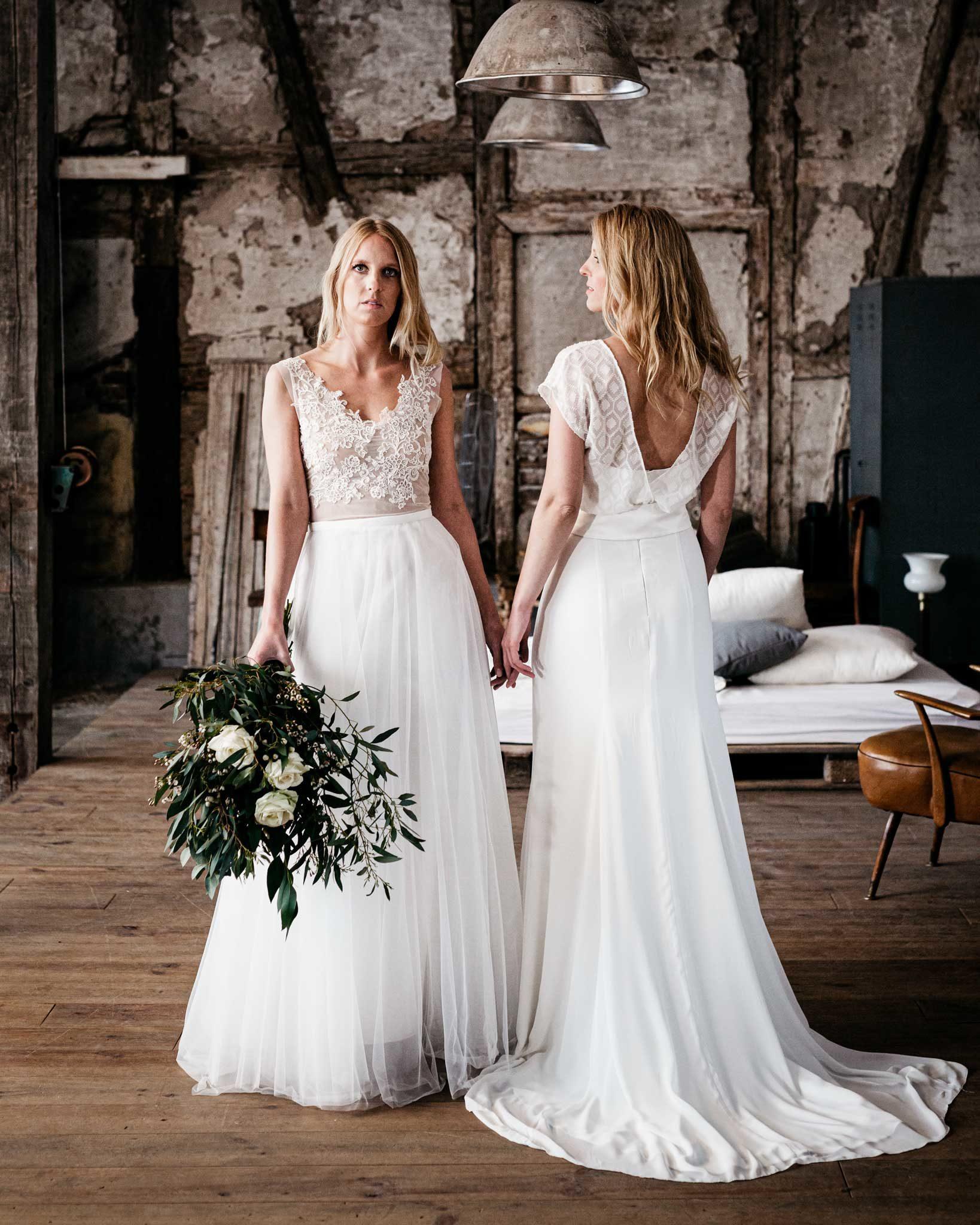 Zwei junge sehr hübsche Frauen stehen nebeneinander in Design Brautkleidern und berühren sich leicht an der Hand. Fotoshoot für die neue Brautkleid-Kollektion von Lena Wolf für 2018.