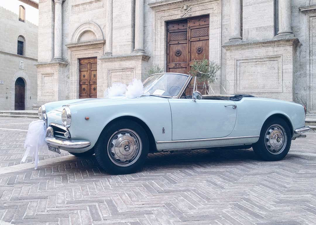 geschmücktes hellblaues Cabrio vor einer Kirche. Hochzeitsauto wartet auf das Brautpaar. Hochzeiten.