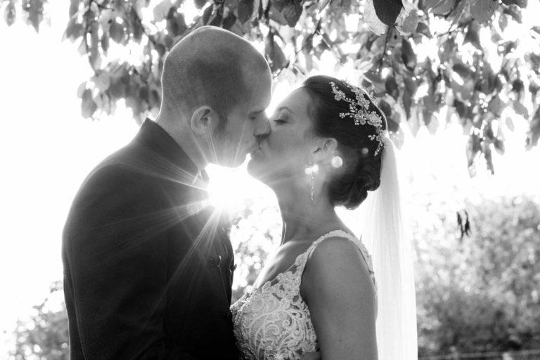 Braut und Bräutigam küssen sich im Gegenlicht, Schwarz-Weiß, mit Lensflare. Hochzeiten