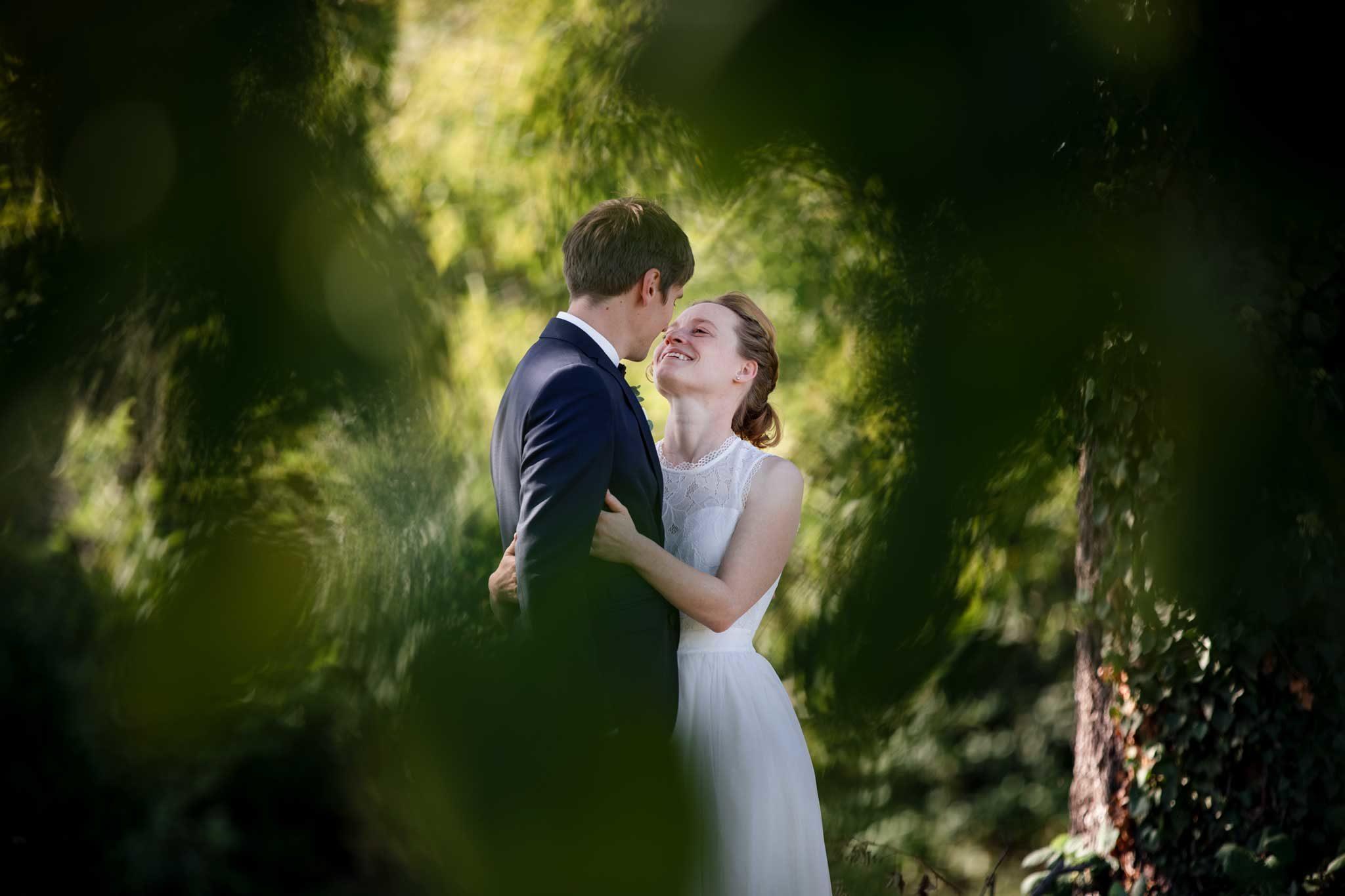 Das Brautpaar steht an einem schattigen Flecken. einfach eine kurze, romantische Auszeit bevor die Feier weitergeht. . Echte Hochzeit in Wiesloch, Brautpaar Fotos im Grünen am Gänsberg, Wiesloch, Braut schaut engumschlungen dem Bräutigam in die Augen. Hochzeiten.