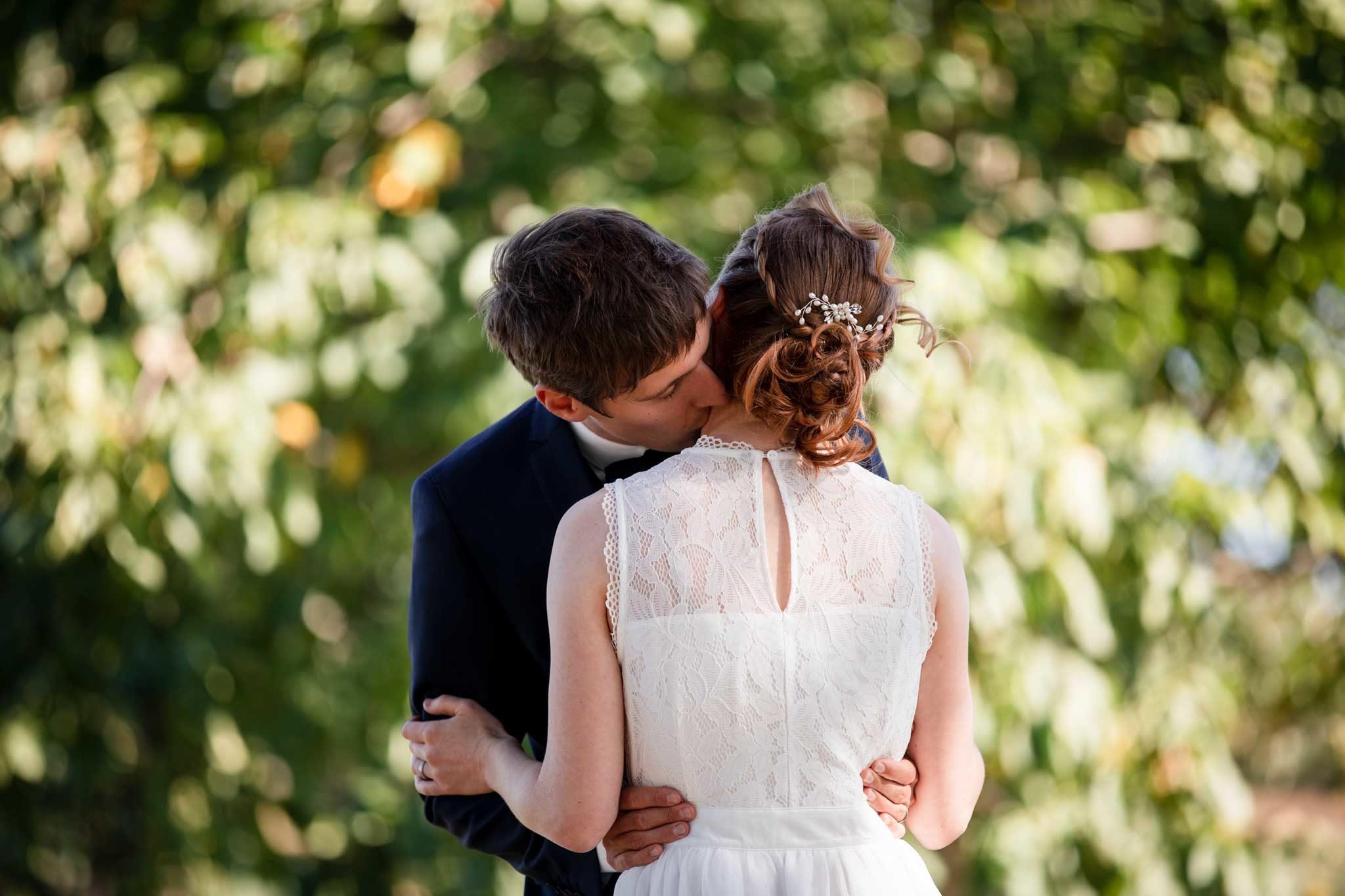 Das Brautpaar steht an einem schattigen Platz auf dem Landgut Lingental. Zweisamkeit pur, einfach eine kurze, romantische Auszeit bevor die Feier weitergeht. . Echte Hochzeit in Wiesloch, Brautpaar Fotos im Grünen am Gänsberg, Wiesloch. Bräutigam küsst Braut auf den Hals.