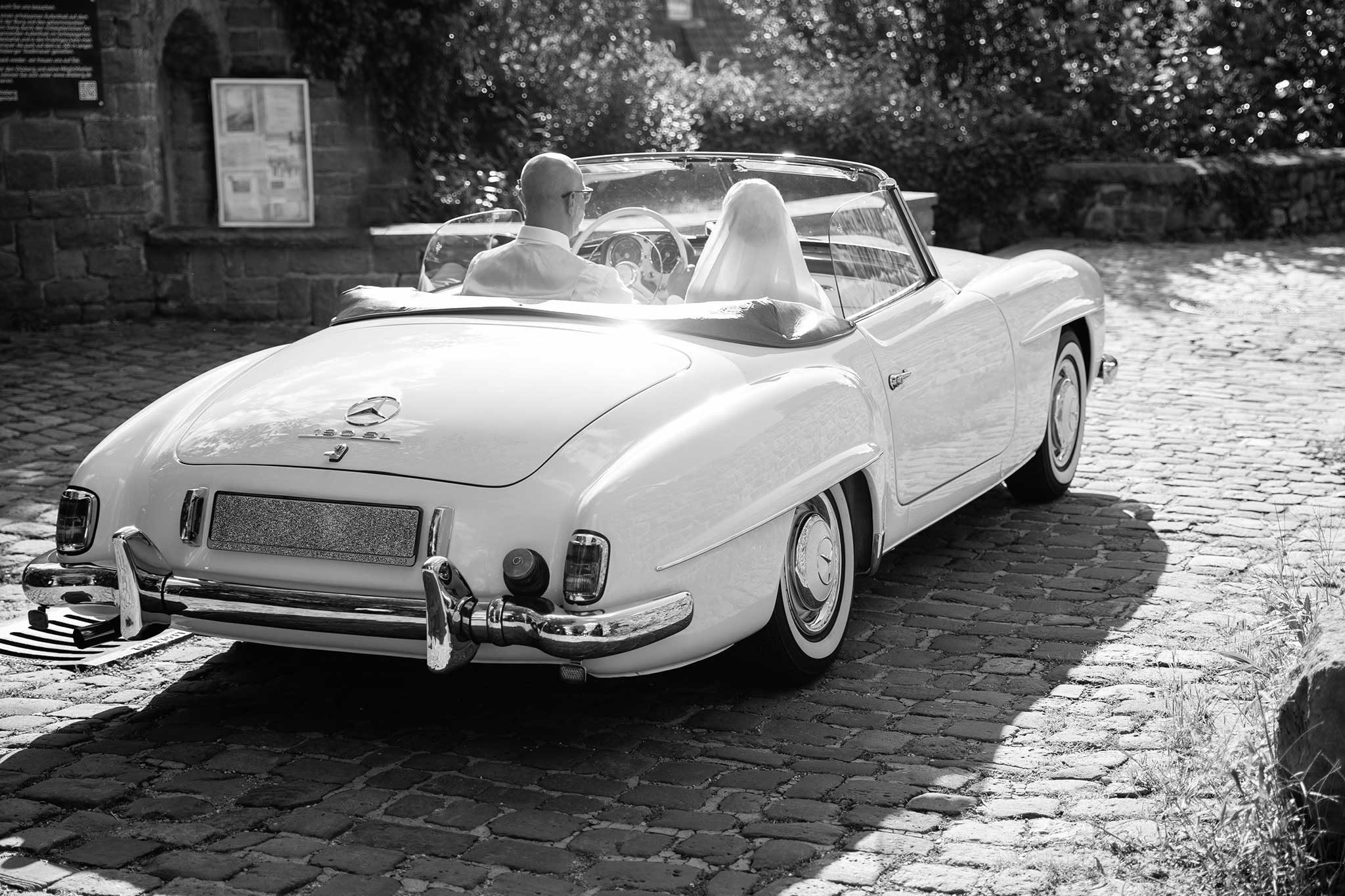 frisch vermähltes Brautpar fährt im weißen Oldtimer Cabrio auf einem Kopfsteinpflaster im Gegenlicht in eine neue Zukunft. Hochzeiten, Portfolio, Hochzeitsauto, 190SL Mercedes-Benz