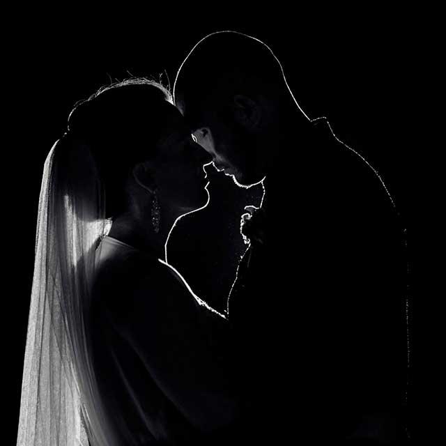 Gegenlicht, Schwarz-Weiß, Nachtaufnahme, Braut und Bräutigam berühren sich umarmt mit den Köpfen und genießen ein paar Minuten Ruhe auf Ihrem Hochzeitstag. Hochzeiten.